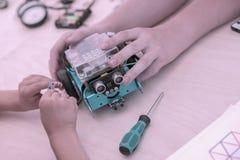 Ręki dzieci zbiera modela kontrolowany terenu pojazd, robić mechaniczna zabawka Pojęcie dzieci obrazy stock