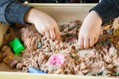 Ręki dziecko bawić się z kinetycznym piaskiem zdjęcia royalty free