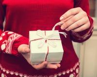 Ręki dziewczyna trzyma boże narodzenie prezenta pudełko z r w czerwonym pulowerze Fotografia Royalty Free