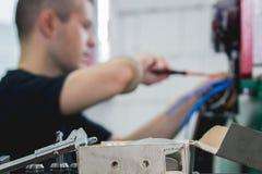 Ręki elektryka inżyniera śrubowanie i probierczy wyposażenie w lontu pudełku, skupiać się Zdjęcie Royalty Free