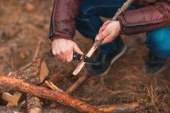 Ręki facet z nożowym zgrzytnięciem gałąź zdjęcie stock