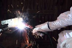 Ręki fachowy przemysłowy spawacz spawa metal stal z iskrze w fabryce z pochodnią i ochronnymi rękawiczkami obrazy stock