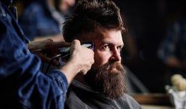 Ręki fryzjer męski z włosianym cążki, zamykają up Modnisia brodaty klient dostaje fryzurę Zakładu fryzjerskiego pojęcie Fryzjer m Obraz Stock