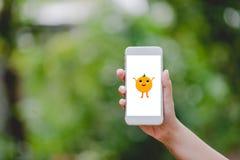 Ręki i telefon pomarańcze Śliczny mały ekran Zielenieją naturę Technolo fotografia stock