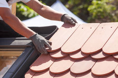 Ręki kłaść płytkę na dachu dacharz Instalować naturalną czerwieni płytkę Zdjęcie Royalty Free