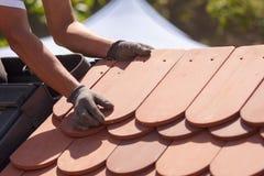 Ręki kłaść płytkę na dachu dacharz Instalować naturalną czerwieni płytkę Obrazy Stock