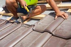 Ręki kłaść płytkę na dachu dacharz Instalować naturalną czerwieni płytkę Fotografia Stock