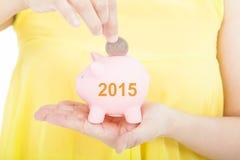 Ręki kładzenia moneta w prosiątko banka dla 2015 inwestyci Zdjęcia Royalty Free