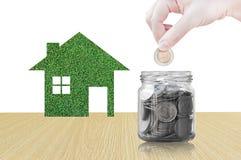 Ręki kładzenia moneta w szklanego zbiornika kupować nowego dom - oszczędzanie pieniądze dla przyszłościowego pojęcia Zdjęcia Royalty Free