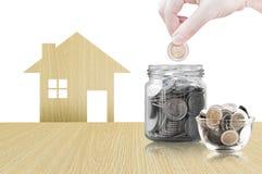 Ręki kładzenia moneta w szklanego zbiornika kupować nowego dom - oszczędzanie pieniądze dla przyszłościowego pojęcia Zdjęcia Stock