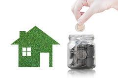 Ręki kładzenia moneta w szklanego zbiornika kupować nowego dom - oszczędzanie pieniądze dla przyszłościowego pojęcia Obrazy Stock
