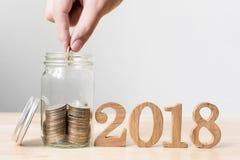 Ręki kładzenia pieniądze moneta w słoju z drewno liczby rokiem 2018, Conce Zdjęcie Royalty Free