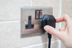 Ręki kładzenia prymka W elektryczności nasadkę Zdjęcie Royalty Free