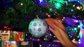 Ręki kobieta dekoruje na choince z boże narodzenie łuną zaświeca zbiory