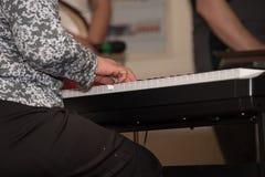 Ręki kobieta w czarnej spódnicie bawić się na synthesiz Zdjęcia Stock