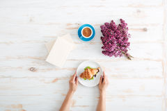 Ręki kobiety łasowania croissant i pić kawa na stole Zdjęcie Stock