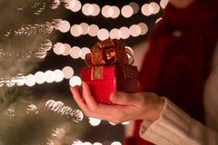 Ręki kobiety chwyta prezenta czerwony Bożenarodzeniowy pudełko na bokeh zaświeca tło Obrazy Royalty Free