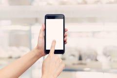 Ręki kobiety mienia telefon z pustym ekranem i plama robi zakupy mal obraz stock