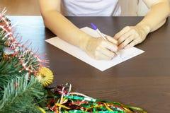 Ręki kobiety obsiadanie stołu i writing bożych narodzeń życzeniami na karcie, list zdjęcia royalty free