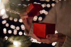 Ręki kobiety otwarcia prezenta Bożenarodzeniowy pudełko z bokeh zaświeca tło Zdjęcie Royalty Free