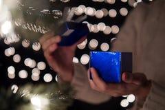 Ręki kobiety prezenta otwarty błękitny Bożenarodzeniowy pudełko z bokeh zaświeca tło Obrazy Stock