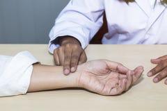 Ręki kobiety profesjonalisty lekarka bierze puls z pacjentem przy szpitalem zdjęcia stock