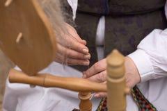 Ręki kobiety przędzalniana wełna w przędzę z przędzalnianym kołem Fotografia Royalty Free