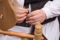 Ręki kobiety przędzalniana wełna w przędzę z przędzalnianym kołem Zdjęcia Royalty Free