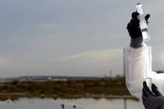 Ręki kontrolują zanieczyszczoną wodę Zdjęcia Stock
