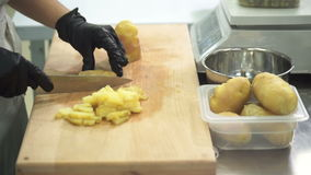 Ręki kucharz w czarnych rękawiczka plasterkach gotowane grule zbiory