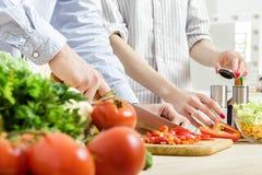 Ręki mężczyzna siekali czerwonego dzwonkowego pieprzu na pokładzie Pary ciapania warzywa w kuchni Obraz Royalty Free