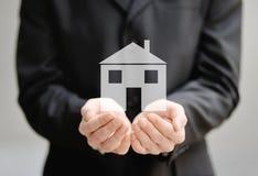 Ręki mężczyzna trzyma dom - ubezpieczenie i ochrony pojęcie Zdjęcia Royalty Free