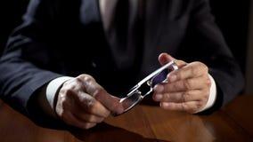 Ręki męscy oficera śledczego mienia eyeglasses, zapytywania przestępstwa podejrzany zdjęcie royalty free