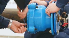 Ręki męscy pracownicy są wodnymi drymbami na dostawa wody systemu zbiory