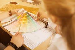 Ręki męski projektant w biurowym działaniu z kolor próbkami Kobieta wybiera colourful papier przy miejscem pracy sporządza mapę z Zdjęcie Royalty Free