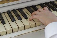 Ręki młoda dziewczyna bawić się na białym pianinie, zakończenie fotografia stock