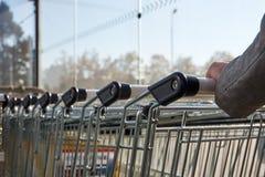 Ręki młoda kobieta trzyma wózek na zakupy w supermarkecie obrazy stock