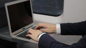 Ręki młody biznesmen który pisać na maszynie emaila na jego laptop klawiaturze podczas gdy podróżujący w pociągu zdjęcie wideo