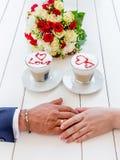 Ręki młodzi kochankowie ludzie zbliżają filiżanki kawy i bouque zdjęcie stock