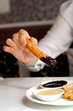Ręki maczania Hiszpańscy churros grzać ciemnego czekoladowego kumberland Zdjęcie Royalty Free