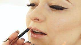 Ręki makeup artysta z kosmetyka muśnięcia obrazu wargami na kobiety twarzy Makeup warg zamknięty up zdjęcie wideo