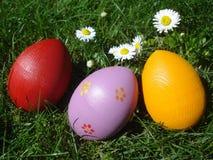 Ręki malujący Wielkanocni jajka na trawie Zdjęcia Stock