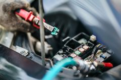 Ręki mechanik zamienia lont w samochodzie Mechanik wybiera poprawnego lont Selekcyjna ostrość Zdjęcie Stock