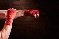 Ręki mięśniowy sportowy mężczyzna z czerwonym bandażem przeciw brown tłu Obraz Stock