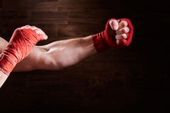 Ręki mięśniowy sportowy mężczyzna z czerwonym bandażem przeciw brown tłu Obrazy Stock