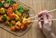 Ręki mienia chopsticks kawałek kurczak Piec na grillu piec warzywa z kawałkami kurczaka curry Obrazy Stock