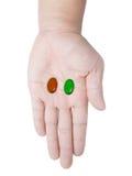 Ręki mienia czerwone i zielone kapsuły Zdjęcia Royalty Free