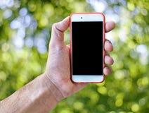 Ręki mienia dotyka ekranu telefon komórkowy odizolowywał zielonego rozmytego tło Obraz Royalty Free