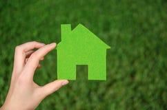 Ręki mienia eco domu ikony pojęcie na zielonej trawy tle Obrazy Royalty Free