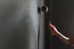 Ręki mienia farby rolownik stosuje popielatą farbę na ścianie Zdjęcie Stock